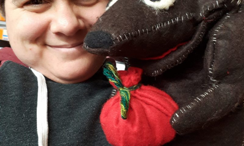 Image shows Director of Religious Education, Ilara Stefaniuk-Gaudet, smiling with a squirrel hand puppet. The Puppet's name is Spruce.